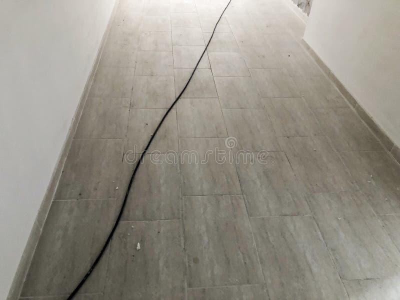 Kabel auf dem Boden Erneuertes Portal in einem Neubau Betonmauern Eben gelegte Fliesen auf dem Boden stockfotografie