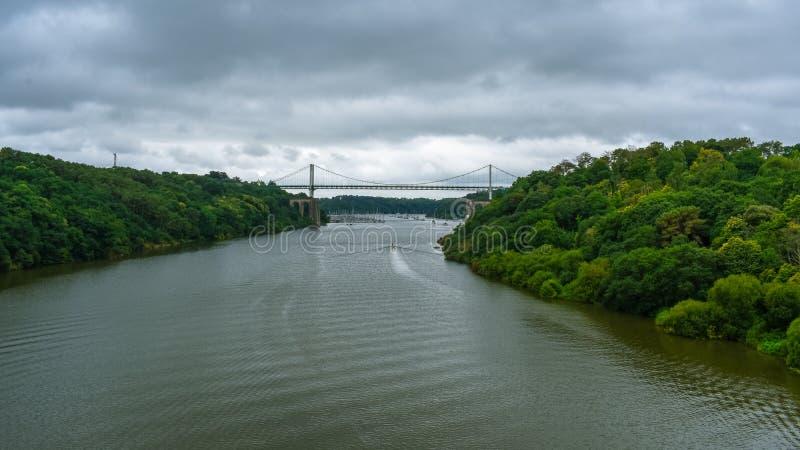 Kabel-gebleven brug in een groen natuurlijk bos, met een dramatische bewolkte hemel Motorboot die op de rivier varen stock foto's