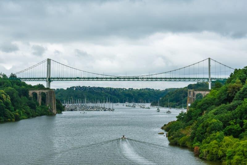 Kabel-gebleven brug in een groen natuurlijk bos, met een dramatische bewolkte hemel Motorboot die op de rivier varen royalty-vrije stock afbeeldingen