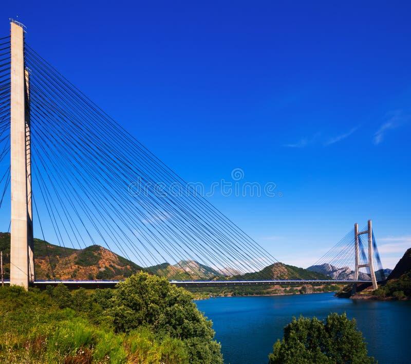 Kabel-gebleven brug over meer in bergen stock foto