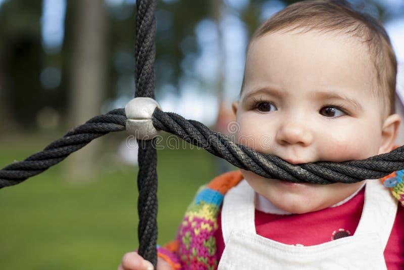 kabel van de het meisjes de bitting speelplaats van de 11 maandbaby aangezien het een teether was stock foto