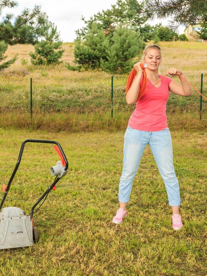 Kabel van de vrouwen de rollende maaimachine in tuin stock foto's