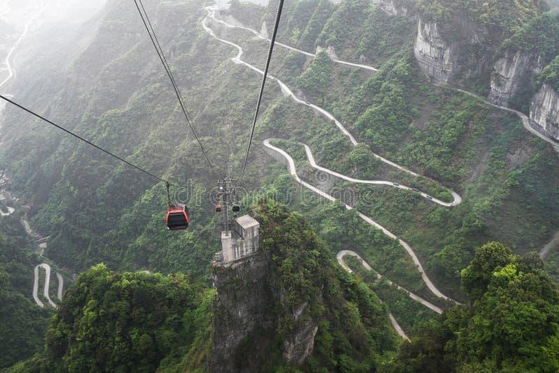 Kabelbil ovanför den slingriga vägen i det Tianmen berget, Kina arkivfoto