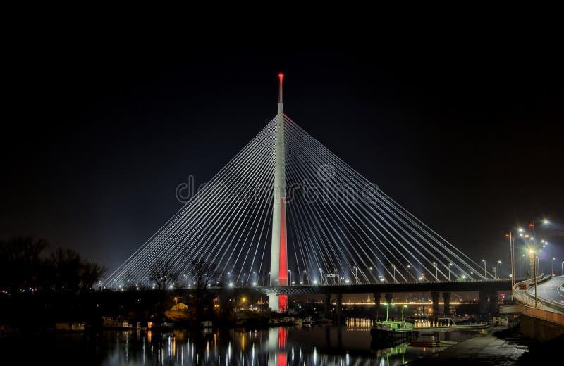 Kabelbron Belgrade på natten med staden tänder arkivfoto