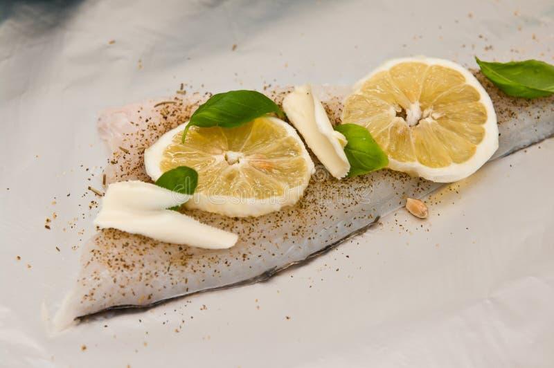 Kabeljauwvisschotel met citroenen en tomaten stock foto