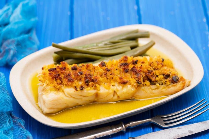 Kabeljauwvissen met graanbrood en slabonen op schotel stock afbeeldingen