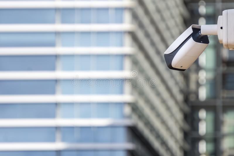 Kabeltelevisie-veiligheidscamera bij de bouw van muur vooraan wolkenkrabber stock foto