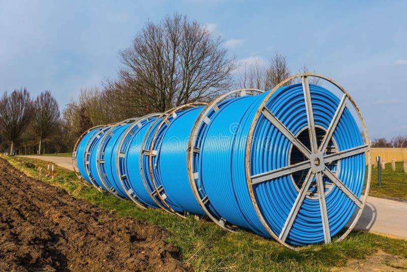 Kabeltrommels met blauwe kabels stock afbeeldingen