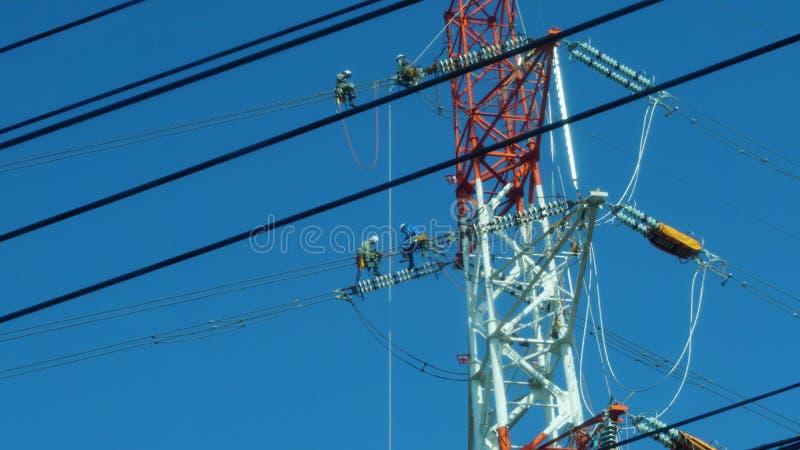 4 kabelunderhållstekniker som sitter på kablarna, Fukuoka royaltyfri fotografi