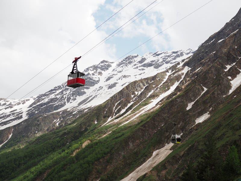 Kabelwagen op de achtergrond van de bergen Oude rode kabelwagen bij berg en gele nieuw Rusland, Elbrus - Juni 2019 stock afbeeldingen