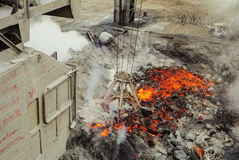 Kabin av travers med mekanisk multivalveclamshellbrottning på en bakgrundsavdunstning av smält vätskeglödhett järn och royaltyfria foton