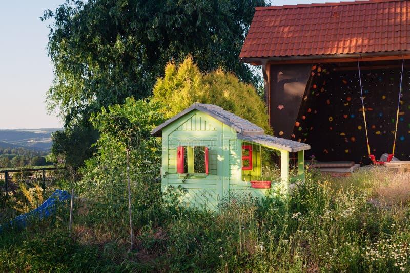 Kabin för lekstuga för barnungehus i trädgård arkivfoton