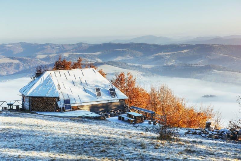 Kabin i bergen i vinter mystisk dimma I anticipatio royaltyfri foto