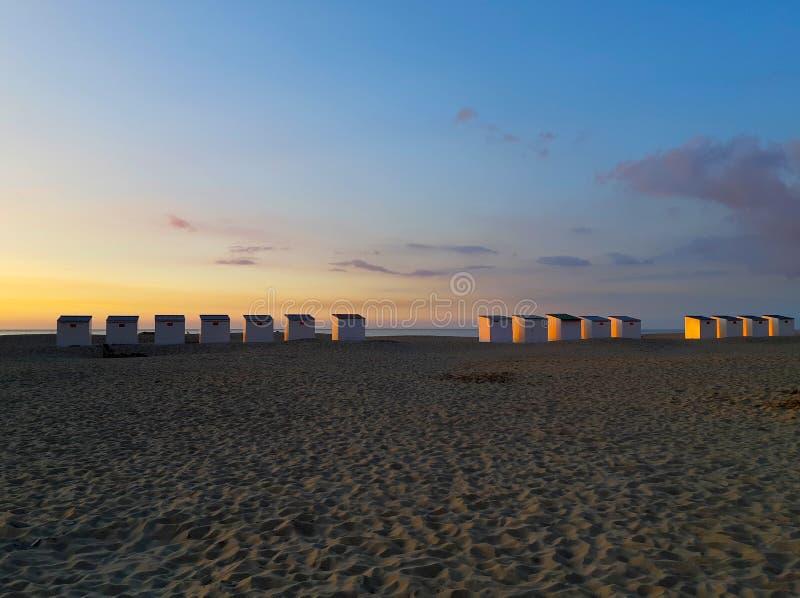 Kabinen auf dem Strand bei Sonnenuntergang stockfotografie