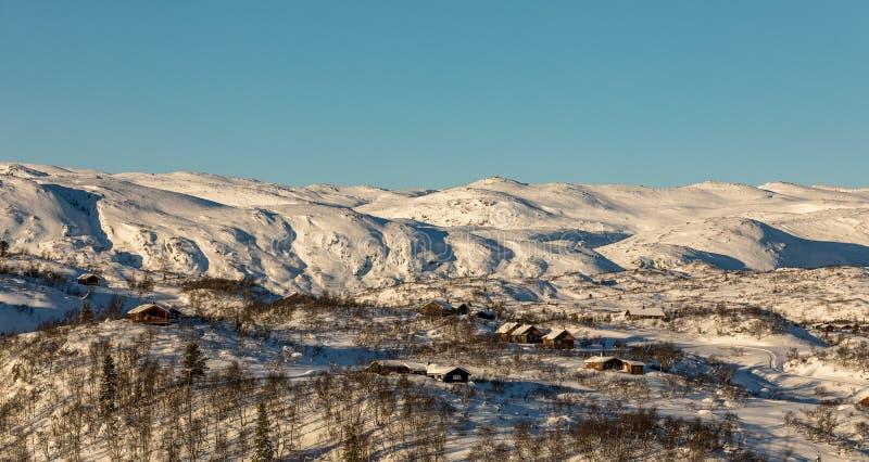 Kabiner i bergen, den blåa himlen, vintern och det insnöat berglandskapet i Brokke, Setesdal i Norge arkivbild