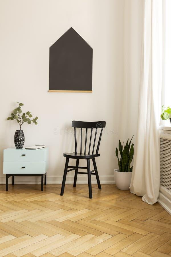 Kabinet naast zwarte stoel in minimaal ruimtebinnenland met affiche en installatie op houten vloer Echte foto stock afbeelding