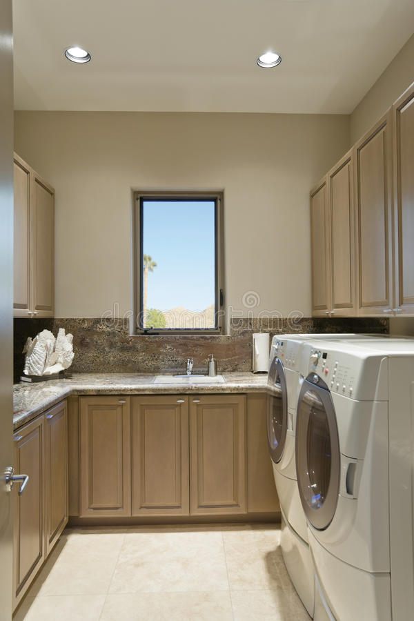 Kabinetter och tvagningmaskin i tvättstuga royaltyfri fotografi