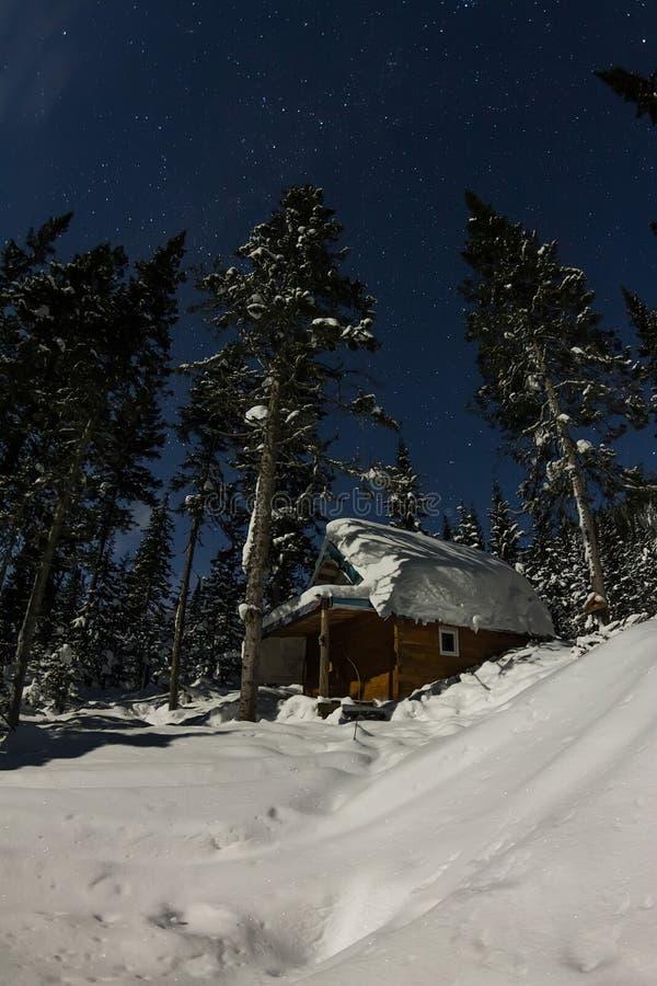 Kabinhuschalet i vinterskog med den insnöade ljusa månen och fotografering för bildbyråer