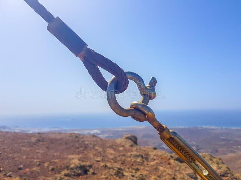Kablar f?r s?kerhetsl?s- och tr?d?gla som gripa in i varandra i f?rgrunden med himmel- och havsbottnar Bild som tas i Lanzarote,  royaltyfri fotografi