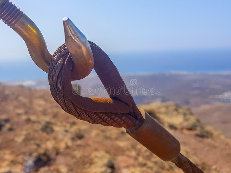 Kablar f?r s?kerhetsl?s- och tr?d?gla som gripa in i varandra i f?rgrunden med himmel- och havsbottnar Bild som tas i Lanzarote,  royaltyfria foton