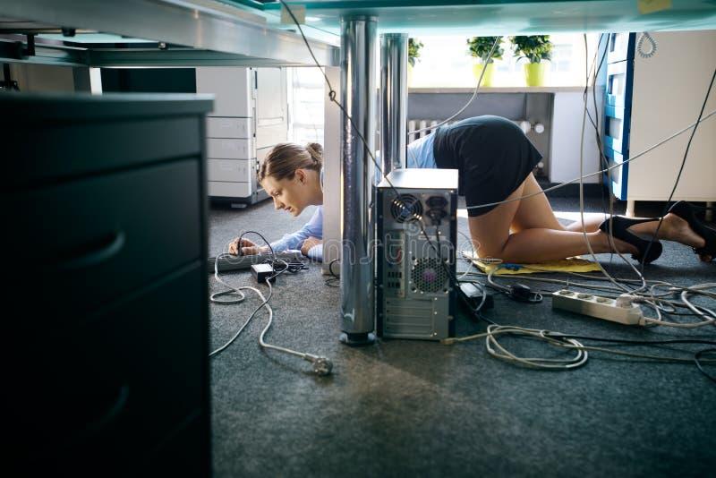 Kablar och trådar för ung arbetare förbindande till datoren i regeringsställning royaltyfria foton