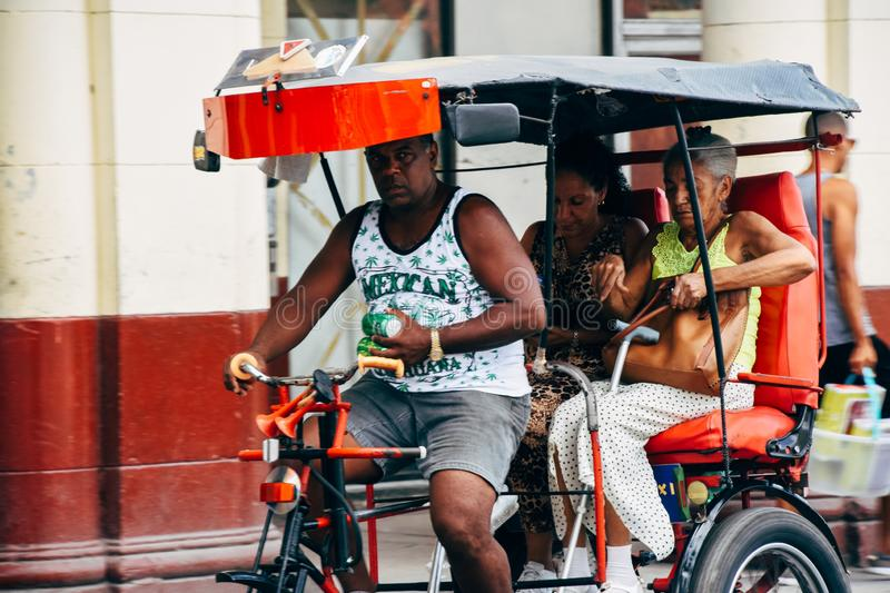 A kabuki driver carries customers to their destination. A kabuki driver carries customers to their destination in Havana, Cuba royalty free stock photo