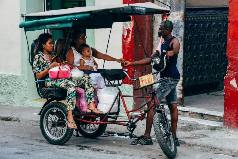 A kabuki taxi drops a family off at their destination in Havana, Cuba. A kabuki taxi driver drops a family off at their destination in Havana, Cuba stock image