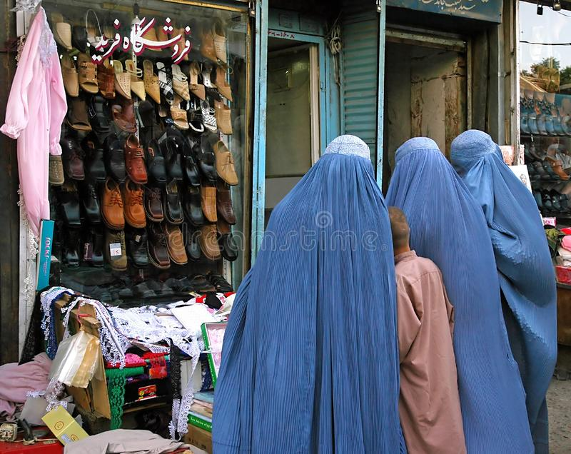Kabul, Afghanistan: Afghan women wearing blue burqas standing outside a shoe store royalty free stock photo