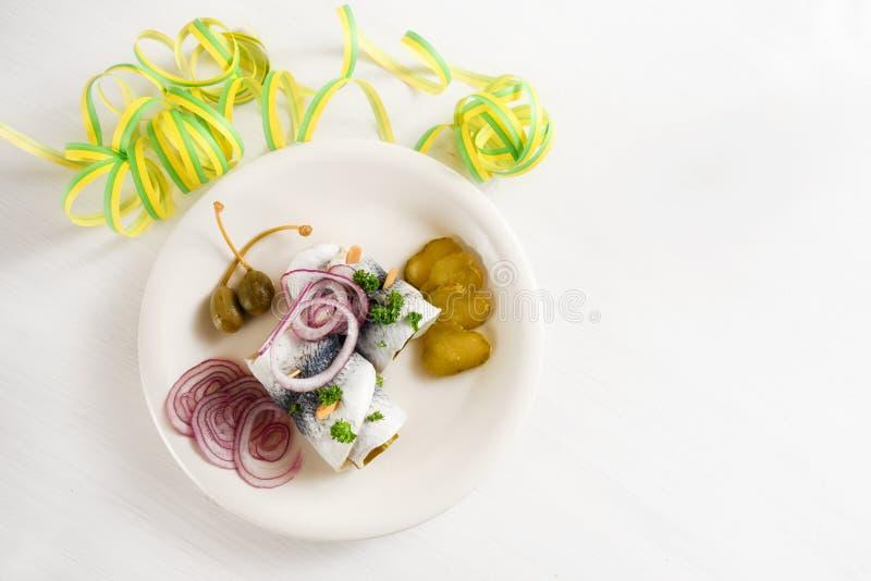 Kac posiłek, staczający się kiszony śledź, także dzwoniący rollmops z czerwonymi cebulami, korniszony i kapary na białym stole z  zdjęcie stock