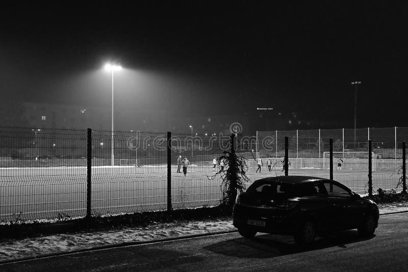 Kadan Tjeckien - januari 24, 2019: fotbollgrad under aftonsnöfall med Opel Astra i förgrund arkivfoto