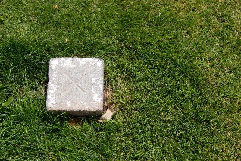 Kadastrale Grenssteen met nauwkeurig kruis in het groene gras stock fotografie