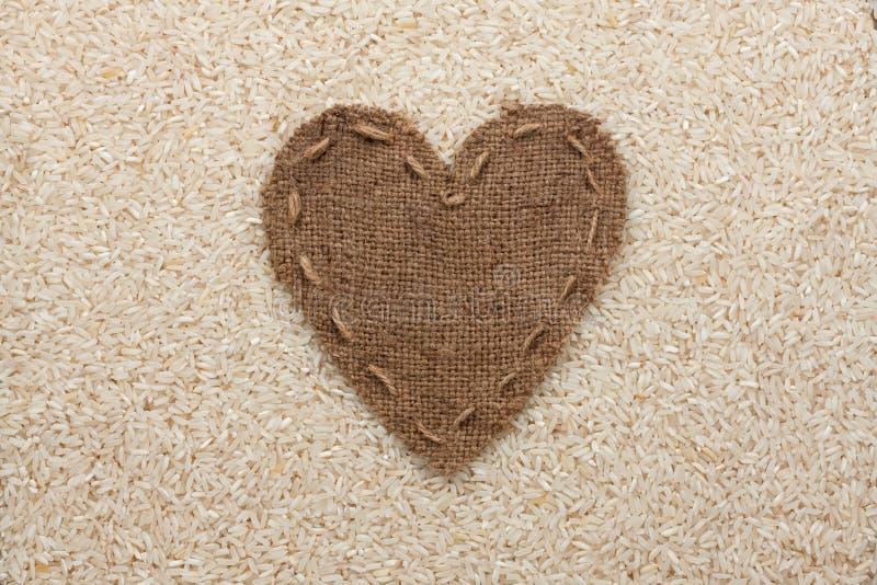 Kader in de vorm van hart van jute met rijst wordt gemaakt die stock foto's