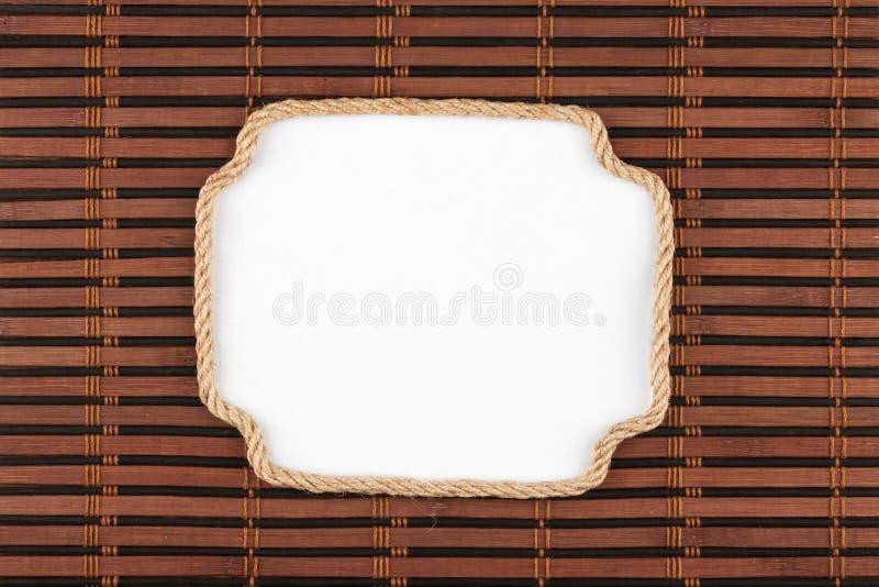 Kader die van kabel op een bamboemat liggen met een witte achtergrond voor uw tekst royalty-vrije stock foto's