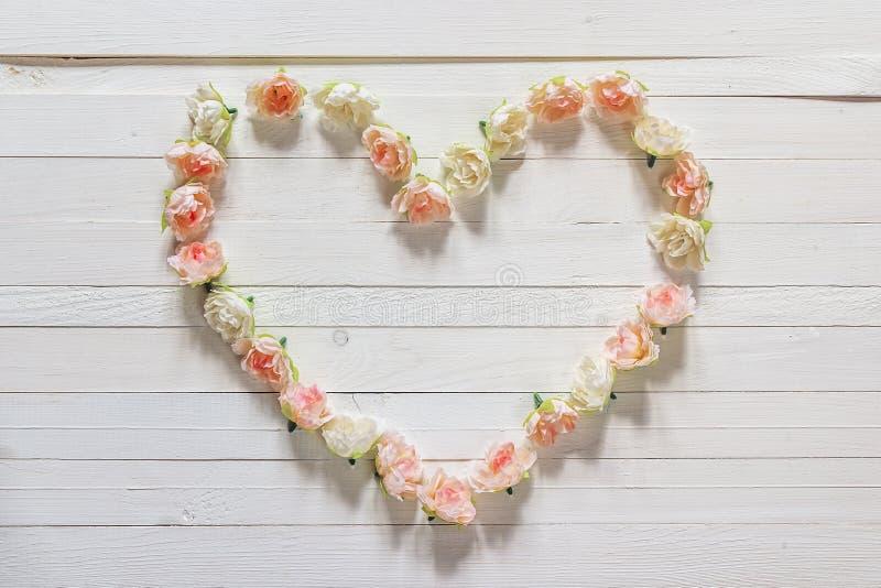 Kader hart-vormige bloemen van rozen op witte houten achtergrond w stock foto's