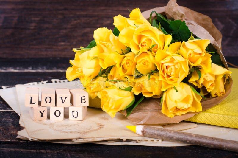 Kader met gele rozen, uitstekend document, notitieboekje en potlood op oude houten achtergrond Vrije ruimte voor uw tekst royalty-vrije stock foto's