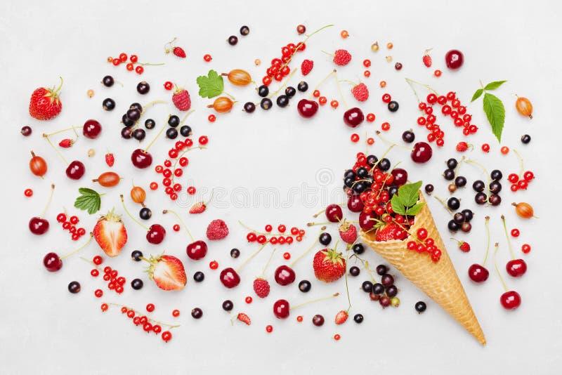 Kader met kleurrijke bessen in wafelkegel op lichte hoogste mening als achtergrond Dieet en gezond dessert Vlak leg het stileren stock fotografie