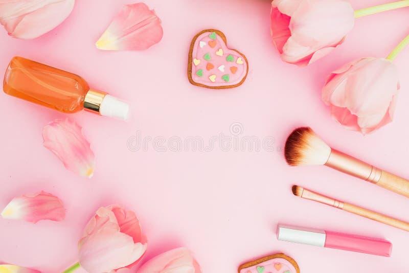 Kader met tulpenbloemen en schoonheidsmiddelen, koekjes op roze pastelkleurachtergrond Vlak leg, hoogste mening met exemplaarruim royalty-vrije stock foto's