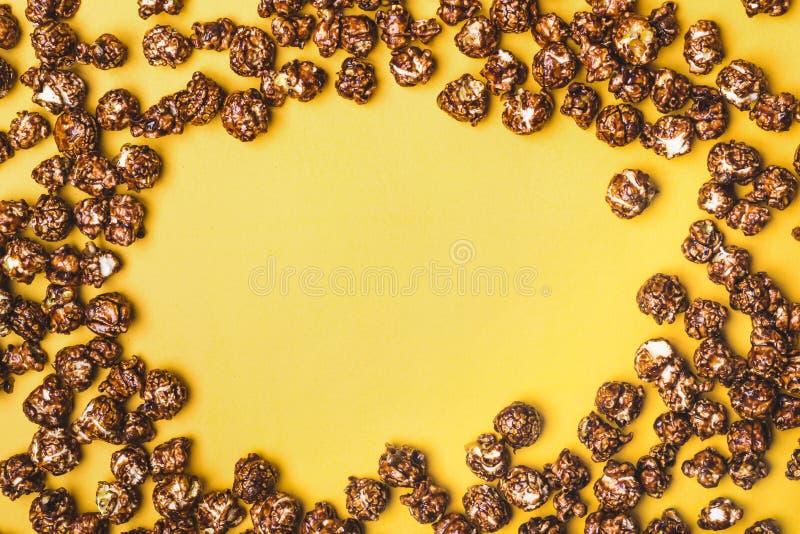 Kader van chocoladepopcorn op een gele achtergrond stock foto's