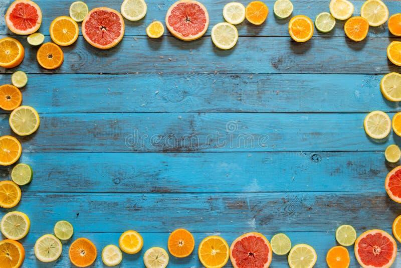 Kader van citrusvruchtenplakken wordt gemaakt op blauwe planken die royalty-vrije stock foto
