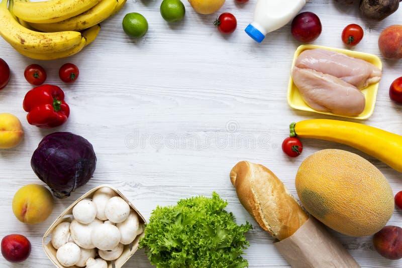 Kader van gezond voedsel op witte houten lijst Kokende voedselachtergrond Vlak leg van verse vruchten, veggies, greens, vlees, me stock fotografie