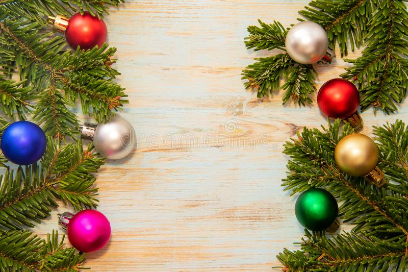 Kader van groene takken van een Kerstboom met veelkleurig speelgoed op een blauwe raad met een plaats voor de inschrijving royalty-vrije stock foto's