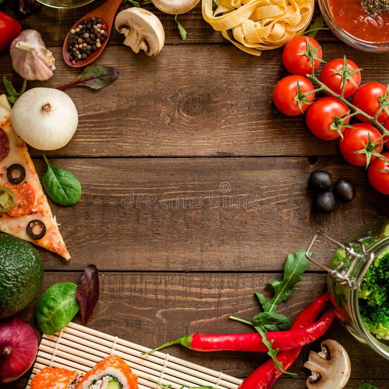 Kader van groenten, pizza, sushibroodjes, tomaat, deegwaren, olijven en saus op houten achtergrond wordt gemaakt die Voedselconce royalty-vrije stock fotografie