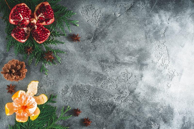 Kader van heerlijke granaat, mandarin kaneel en anijsplant op donkere achtergrond Nieuw jaarconcept, exemplaarruimte Vlak leg Hoo stock foto's