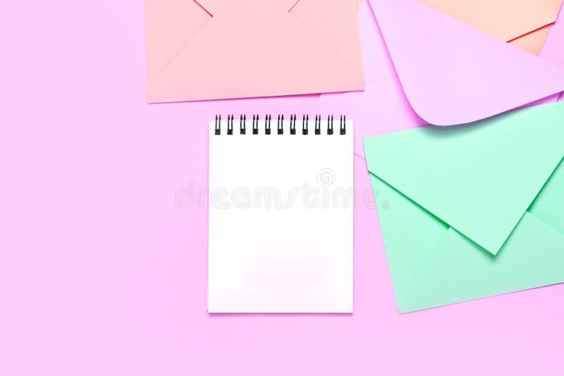 Kader van kleurrijke enveloppen en notitieboekje op de roze mening van de lijstbovenkant stock afbeeldingen