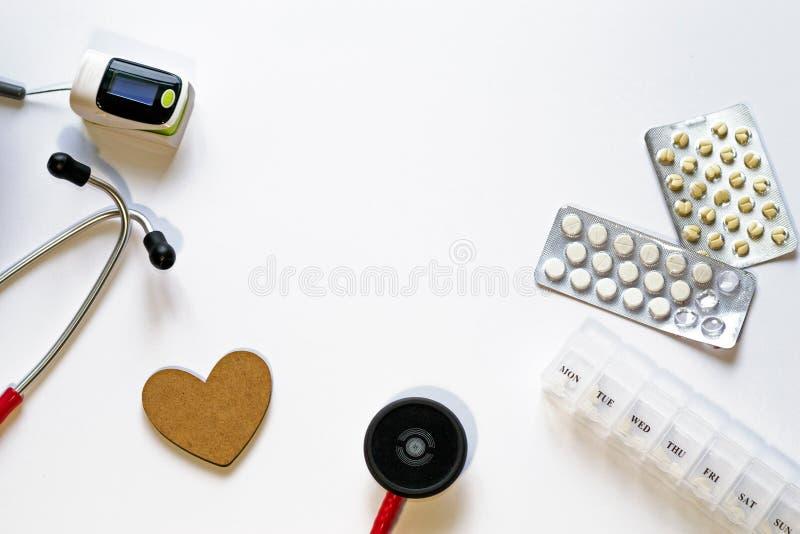 Kader van medische instrumenten, pillen, stethoscoop, impulsoximeter, houten hart, pillenblaren en container op witte achtergrond royalty-vrije stock foto