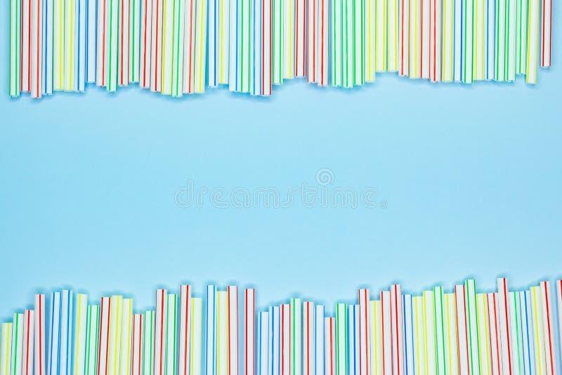Kader van multicolored gestreept plastic stro op een blauwe achtergrond met exemplaarruimte Recyclerend afval stock afbeelding