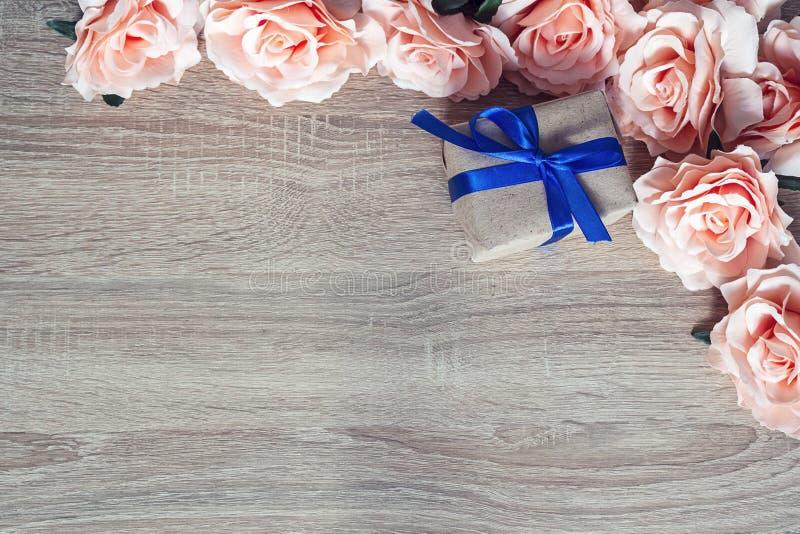 Kader van roze rozen op een houten achtergrond met giftdoos en emp stock fotografie