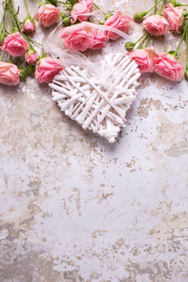 Kader van roze rozenbloemen en decoratief hart royalty-vrije stock afbeeldingen
