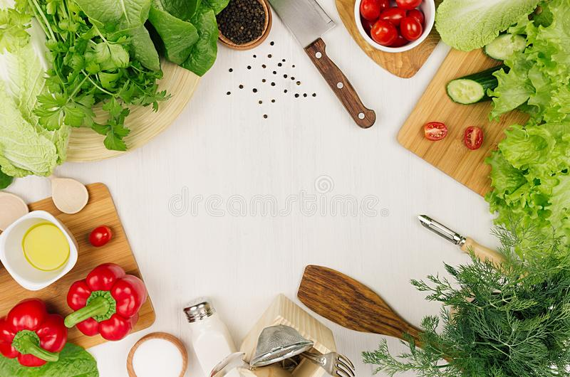 Kader van verse groene salade, rode paprika, kersentomaat, peper, olie en keukengerei op zachte witte houten raad stock foto