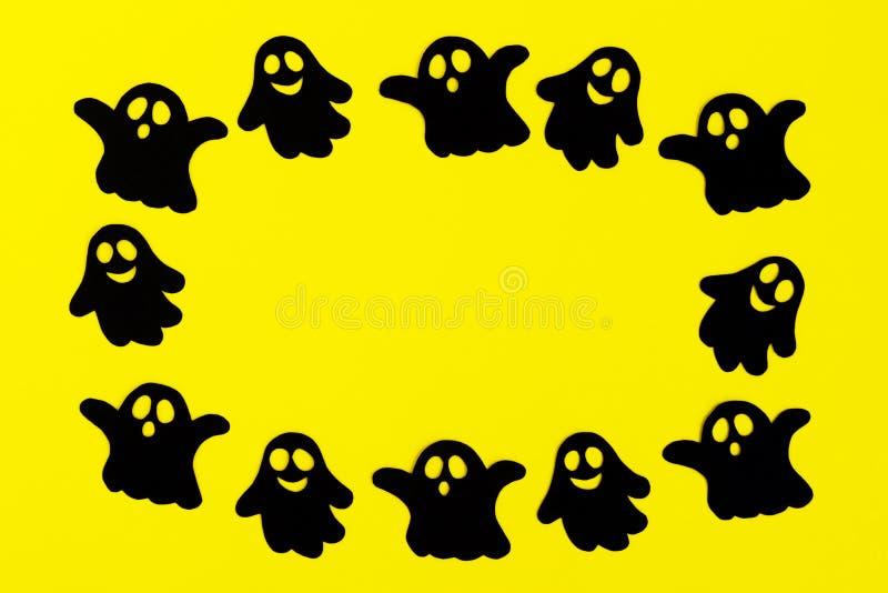 Kader van zwarte document spoken op een gele achtergrond Vakantiedecoratie voor Halloween met exemplaarruimte stock foto